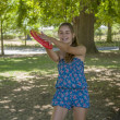 Stock Photo: Young womoutdoor tossing frisbee
