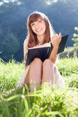 Girl with a book on sunny meadow looking up and smiling — Stock Photo