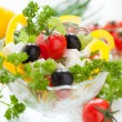 Greek salad in a transparent bowl - Stock Photo