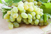 Bunch of golden muscat on a wooden surface, grape — Stock Photo