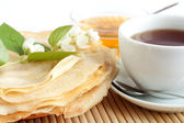 Pancakes with honey and black tea in a white cup — Stock Photo