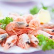 Many great shrimp on white plate with greens — Stock Photo