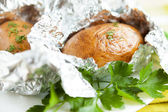 Potatoes in foil, and in a jacket — Stock Photo