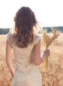 Girl's back in a wheat field with ears of wheat in the hands — Stock Photo