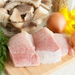 Raw meat on the board, and other ingredients - Stock Photo