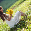 Girl with flowers sitting on the grass — Stock Photo