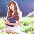 Girl reads a book on the nature — Stock Photo