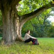 Man is sitting resting under a large old oak tree — Stock Photo