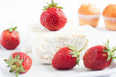 Large piece of cheese and ripe strawberries — Stock Photo