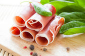 Ham rolled into a tube and green spinach — Stock Photo
