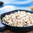 Raw corn and popcorn in a frying pan — Stock Photo