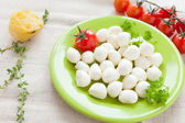 Balls of mozzarella cheese on a green dish — Stock Photo