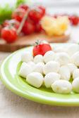 Balls of mozzarella cheese and cherry tomatoes — Stock Photo