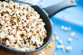 Popcorn in a pan on a blue cloth — Stock Photo