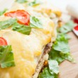 Vegetable lasagna with tomato on top - Stock Photo