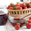 Stock Photo: Strawberry jam on a background of fresh strawberries