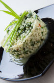 Risotto with spinach and green onions on a black plate — Stock Photo