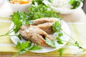 Two pieces of fried fish on a white plate with greens — Stock Photo