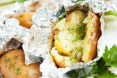 Baked potatoes with dill in foil — Stock Photo