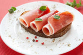 Slices of delicious ham rolled into a tube on a plate — Stock Photo