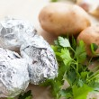 Three potatoes in foil and a bunch of parsley - Stock Photo