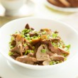 Постер, плакат: Stewed chanterelles with green onions in a white bowl