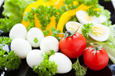 Fresh vegetables on a dish and quail eggs — Stock Photo