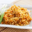 Постер, плакат: Rice with green onions and brown bread on a white square plate