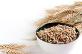 Wheat flakes and wheat spikelets — Stock Photo