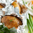 Jacket potatoes cooked in foil, and greens — Stock Photo