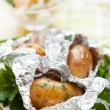 Potatoes in foil not a white plate and a bowl of salad - Stock Photo