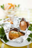 Potatoes in foil not a white plate and a bowl of salad — Stock Photo