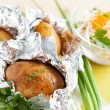 Jacket potatoes baked in foil, and greens - Stock Photo