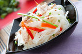 Rice noodles with peppers and tuna in a black bowl — Stock Photo
