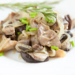 Oyster mushrooms and onions on a white dish - Stock Photo