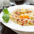 Spaghetti carbonara with yolk and parmesan cheese in a white bow — Stock Photo