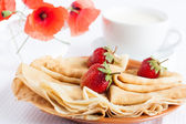 Ruddy pancakes, strawberries on top and a cup of milk — Stock Photo