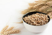 Raw flakes in a white bowl and ears of wheat — Stock Photo