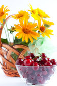 Summer Arrangement - ripe cherries and a bouquet of flowers — Stock Photo