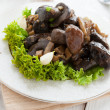 Boletus fried with vegetables on a white plate — Stock Photo