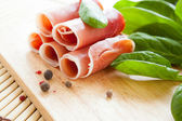 Slices of ham and an armful of greens on a wooden board — Stock Photo
