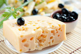Piece of cheese with holes — Stock Photo