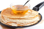 Round pancakes in a frying pan and honey — Stock Photo