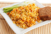 Rice with green onions and brown bread on a white square plate — Stock Photo