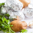 Raw potatoes and greens and foil - Stock Photo