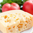 Chunk of cheese on a background of red tomatoes — Stock Photo