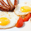 Fried eggs and fried sausage for breakfast — Stock Photo #22585569