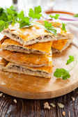 Delicious meat pie slices and parsley — Stock Photo
