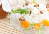Cheese with raisins and dried apricots on a plate — Stock Photo