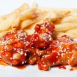 French fries and chicken in tomato sauce — Stock Photo